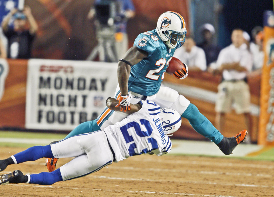Photo - Miami's Ronnie Brown is taken down on the dirt portion of Land Shark Stadium during the Monday Night Football game on Sept. 21. OU will play on the field against the University of Miami on Oct. 3, but there's a chance the dirt will be removed by then. AP PHOTO