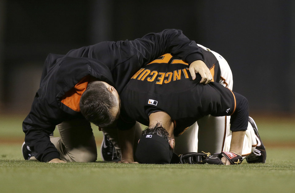 Photo - San Francisco Giants pitcher Tim Lincecum, right, is tended to by trainer Dave Groeschner after being struck by a ball hit by Oakland Athletics' Daric Barton during the fourth inning of an exhibition baseball game in San Francisco, Friday, March 28, 2014. (AP Photo/Jeff Chiu)