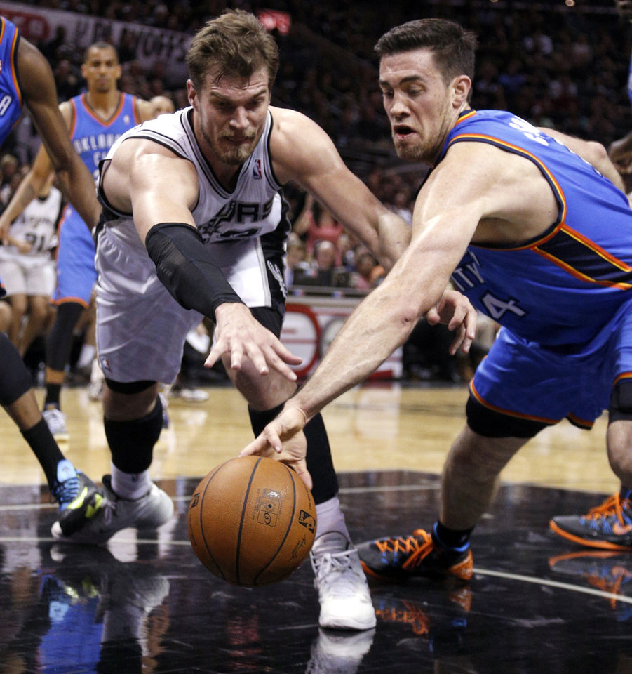Photo - Oklahoma City's Nick Collison (4) and San Antonio's Tiago Splitter (22) fight for a loose ball during Game 1 of the Western Conference Finals in the NBA playoffs between the Oklahoma City Thunder and the San Antonio Spurs at the AT&T Center in San Antonio, Monday, May 19, 2014. Photo by Sarah Phipps, The Oklahoman