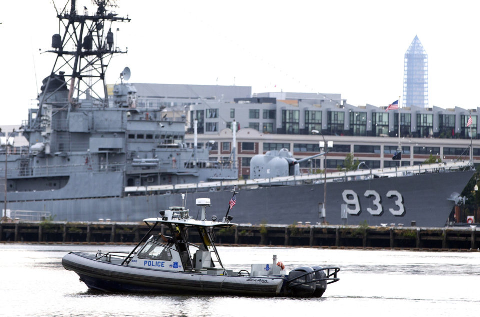 Photo - A police boat patrols near the scene of a shooting at the Washington Navy Yard on Monday, Sept. 16, 2013, in Washington. At least one gunman opened fire inside a building at the Washington Navy Yard on Monday morning. (AP Photo/ Evan Vucci)