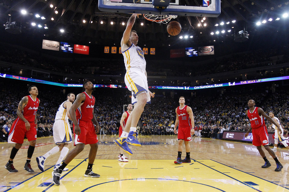 Photo - Golden State Warriors' David Lee, center, dunks against the Los Angeles Clippers during the second half of an NBA basketball game on Thursday, Jan. 30, 2014, in Oakland, Calif. Golden State won 111-92. (AP Photo)
