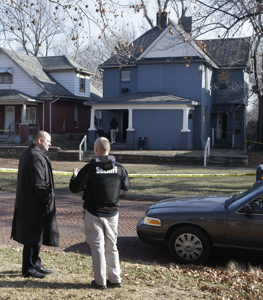 Photo - Investigators talks while standing across the street from a house where a man suspected of fatally shooting two police officers had stayed after the crimes, in Topeka, Kan., Monday, Dec. 17, 2012. The Kansas Bureau of Investigation identified the man who opened fire on Topeka police Cpl. David Gogian, 50, and Officer Jeff Atherly, 29, on Sunday night as 22-year-old David Tiscareno of Topeka. (AP Photo/Orlin Wagner)