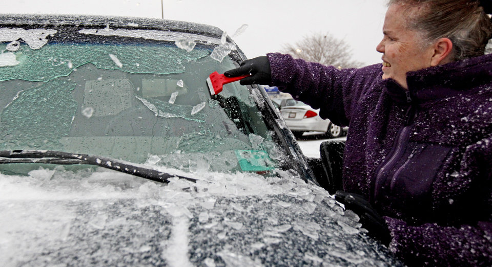Debbie Shaw of Oklahoma City breaks ice off her windshield in Oklahoma City, Thursday, Jan. 28, 2010.  Photo by Bryan Terry, The Oklahoman
