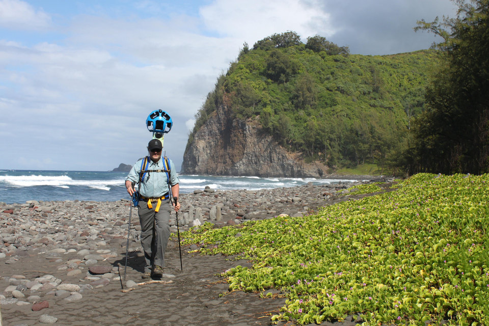 Photo - In this undated photo provided by Google, Rob Pacheco, president of Hawaii Forest & Trail, walks across the beach at Pololu Valley near Kapaau, Hawaii, while wearing the Street View Trekker. Hawaii's volcanoes, rainforests and beaches will soon be visible on Google Street View. The Mountain View, Calif., company said Thursday June 27, 2013 it was lending its backpack cameras to a Hawaii trail guide company to capture panoramic images of Big Island hiking trails. (AP Photo/Google)