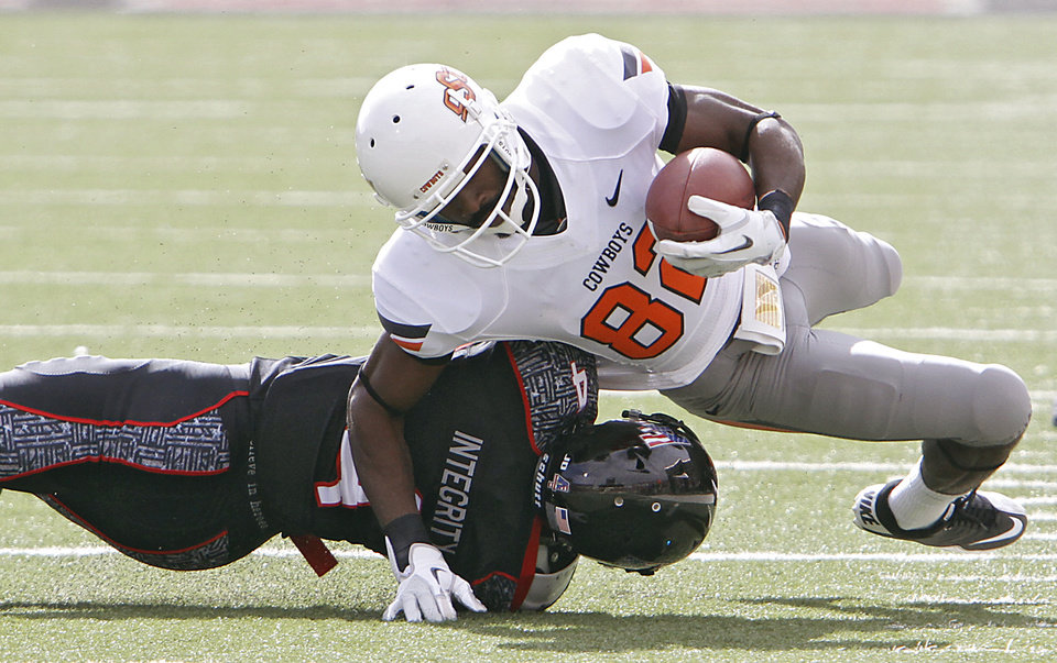 Oklahoma State Cowboys wide receiver Isaiah Anderson (82) is brought down by Texas Tech Red Raiders cornerback Derrick Mays (4) during the college football game between the Oklahoma State University Cowboys (OSU) and Texas Tech University Red Raiders (TTU) at Jones AT&T Stadium on Saturday, Nov. 12, 2011. in Lubbock, Texas.  Photo by Chris Landsberger, The Oklahoman  ORG XMIT: KOD