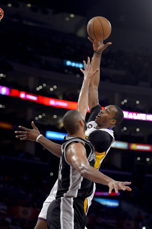 Photo - Los Angeles Lakers center Dwight Howard, right, shoots as San Antonio Spurs forward Tim Duncan defends during the first half in Game 4 of a first-round NBA basketball playoff series, Sunday, April 28, 2013, in Los Angeles. (AP Photo/Mark J. Terrill)