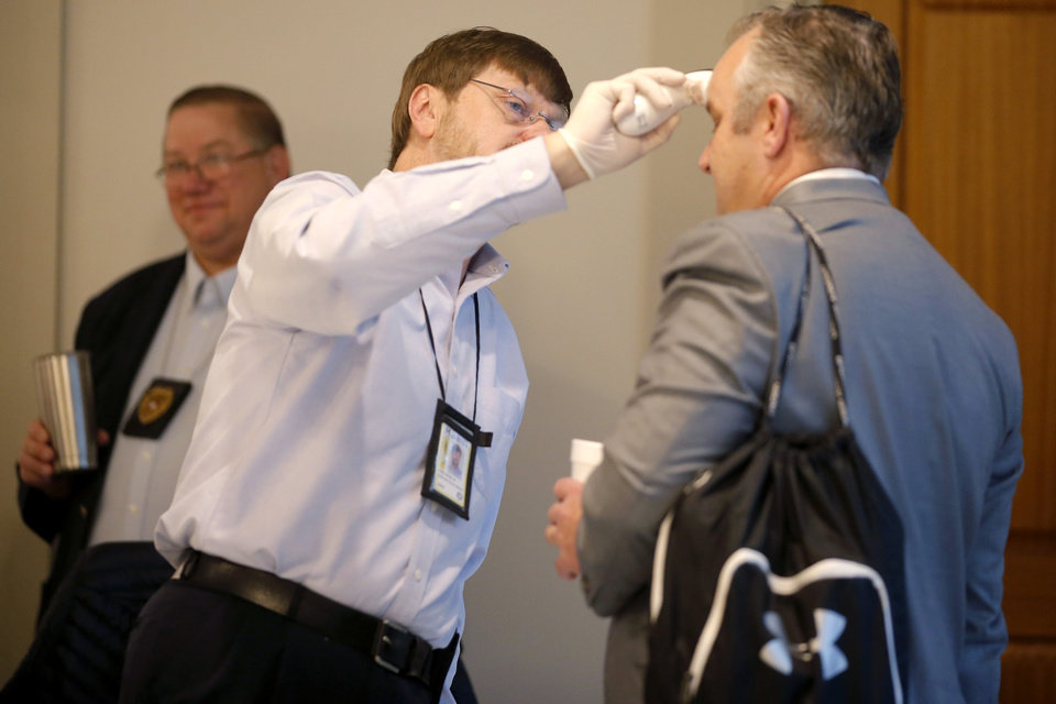 Photo - Phillip Parker with the Oklahoma State Department of Health checks the temperature of Sen. Greg Treat as he enters the state Capitol in Oklahoma City, Monday, April 6, 2020. [Bryan Terry/The Oklahoman]
