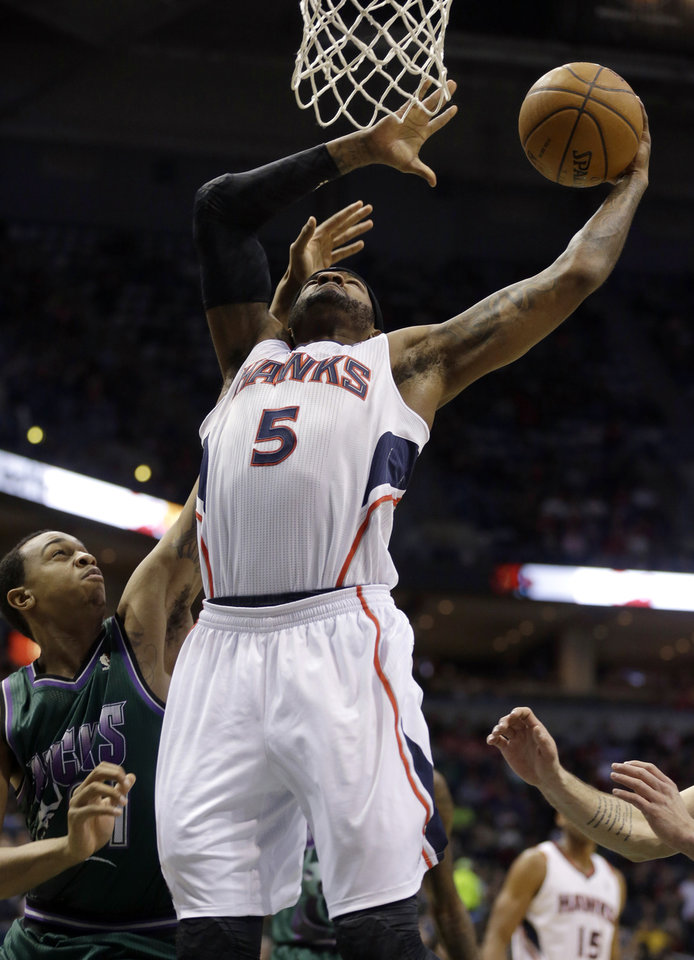 Atlanta Hawks' Josh Smith (5) puts up a shot against Milwaukee Bucks' John Henson, left, during the first half of an NBA basketball game, Saturday, Feb. 23, 2013, in Milwaukee. (AP Photo/Jeffrey Phelps)