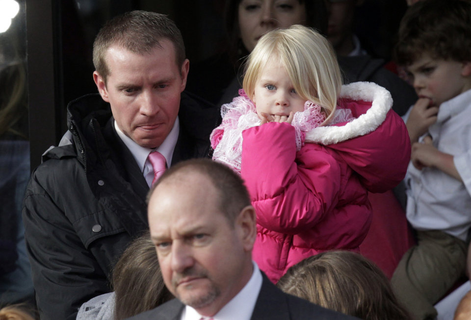 ADDS NAME TO DAUGHTER - Robbie Parker, left, carries his daughter, Madeline, 4, following funeral services for his 6-year old daughter, Connecticut elementary shooting victim Emilie Parker, Saturday, Dec. 22, 2012, at The Church of Jesus Christ of Latter-day Saints, in Ogden, Utah. Emilie, whose family has Ogden roots, was one of the victims killed in a Dec. 14 mass shooting at Sandy Hook Elementary in Newtown, Conn. (AP Photo/Rick Bowmer) ORG XMIT: UTRB104