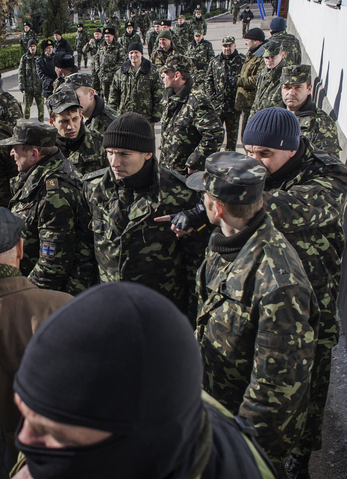 Photo - Ukrainian servicemen stand, with a Crimean self-defense forces member in front, outside the Ukrainian navy headquarters in Sevastopol, Crimea, Wednesday, March 19, 2014. Crimea's self-defense forces on Wednesday stormed the Ukrainian navy headquarters in the Black Sea port of Sevastopol, taking possession without resistance a day after Russia signed a treaty with local authorities to annex the region.  (AP Photo/Andrew Lubimov)