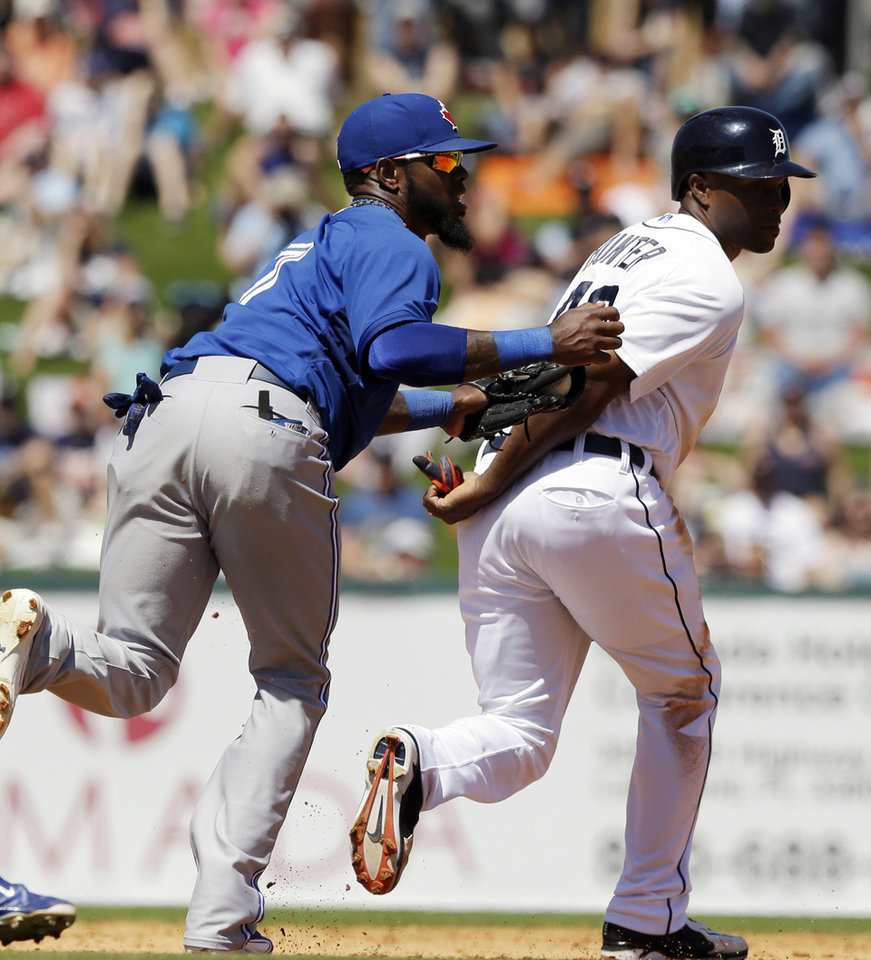 Photo - Detroit Tigers right fielder Torii Hunter, right, is tagged out by Toronto Blue Jays shortstop Jose Reyes on a rundown between second and third during the third inning of a spring exhibition baseball game in Lakeland, Fla., Tuesday, March 18, 2014. (AP Photo/Carlos Osorio)