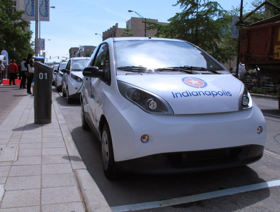 Photo - Electric cars known as Bluecars are lined up in downtown Indianapolis at a car-charging station that debuted on Monday, May 19, 2014, and is part of an electric car-sharing service coming to Indiana's capital. French company Bollore Group is investing $35 million in the project that won't be up and running until year's end, when 125 cars will be available at 25 charging sites around the city. (AP Photo/Rick Callahan.)