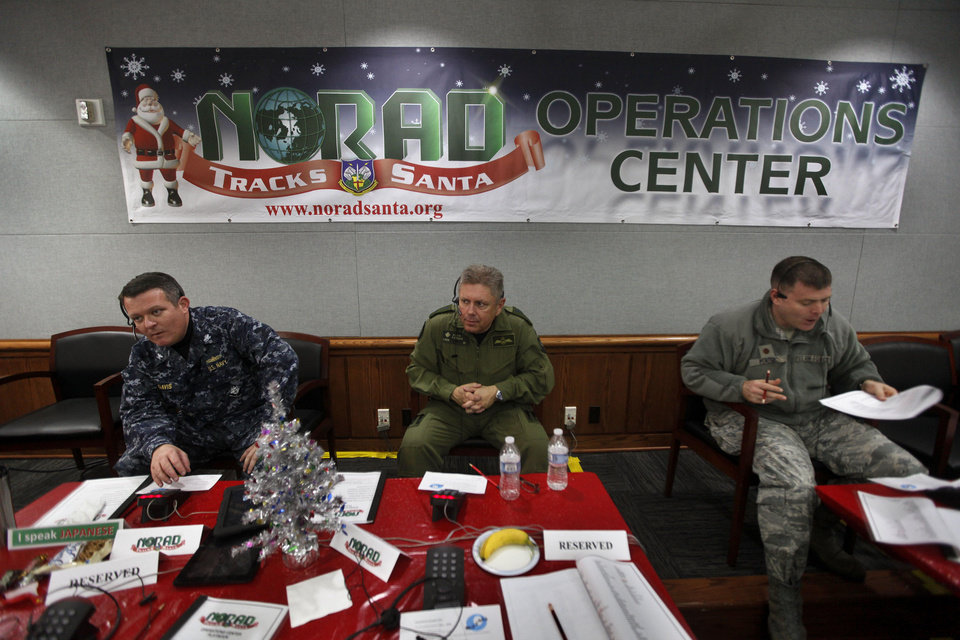 Photo - FILE - In this Dec. 24, 2012 file photo, NORAD Deputy Commander Lt. General Alain Parent, center, of the Royal Canadian Air Force, takes phone calls from children asking where Santa is and when he will deliver presents to their house, during the annual NORAD Tracks Santa Operation, at the North American Aerospace Defense Command, or NORAD, at Peterson Air Force Base, in Colorado Springs, Colo. Also fielding calls are U.S. Navy Capt. Jeff Davis, left, and U.S. Air Force Maj. Chris Bendig. The U.S. and Canadian military will entertain millions of kids again this Christmas Eve with second-by-second updates on Santa's global whereabouts.(AP Photo/Brennan Linsley, File)