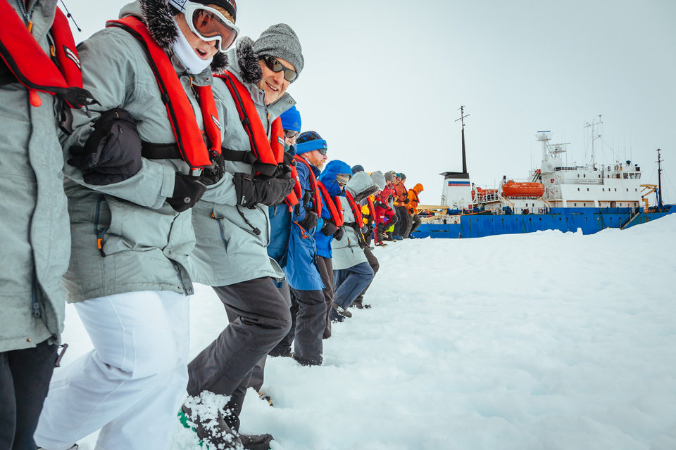 Photo - In this Tuesday, Dec. 31, 2013 image provided by Australasian Antarctic Expedition/Footloose Fotography, passengers from the Russian ship MV Akademik Shokalskiy link arms and stamp out a helicopter landing site on the ice near the trapped ship 1,500 nautical miles south of Hobart, Australia. Passengers on board a research ship that has been trapped in Antarctic ice for a week are expected to be rescued by helicopter, after three icebreakers failed to reach the paralyzed vessel, officials said Tuesday.  (AP Photo/Australasian Antarctic Expedition/Footloose Fotography, Andrew Peacock) EDITORIAL USE ONLY
