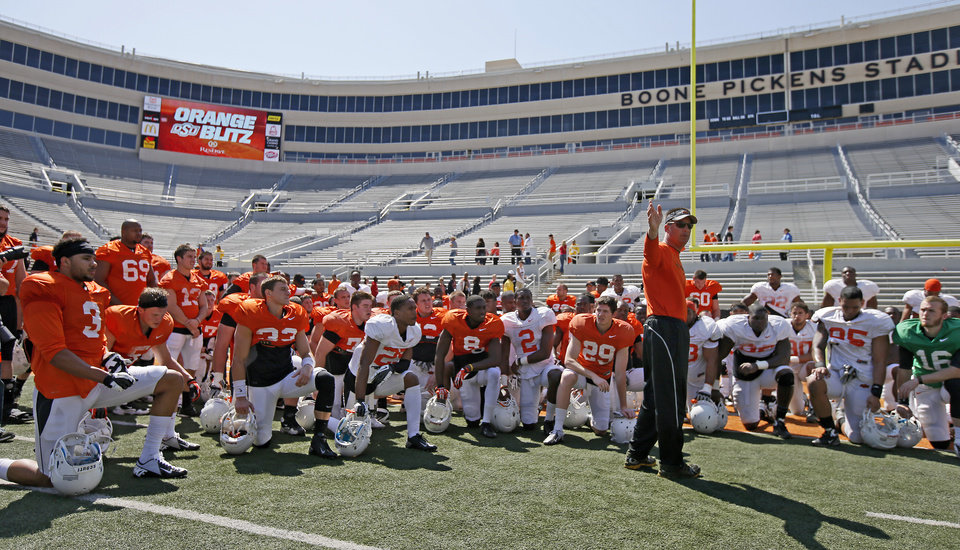 Photo - OSU coach Mike Gundy talks with his players after Oklahoma State's Orange Blitz football practice at Boone Pickens Stadium in Stillwater, Okla., Saturday, April 5, 2014.