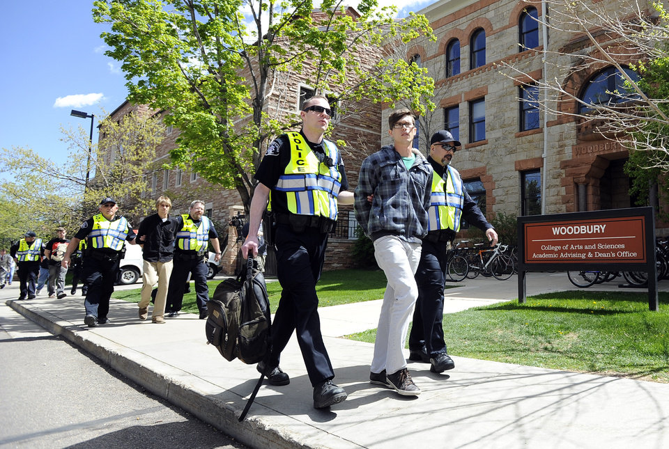 Photo -   University of Colorado senior Jonathan Edwards, right, senior John Demopoulos, middle, and senior Gabriel Kuettel is arrested by Boulder County Sheriff deputies for trespassing on the Norlin Quad by going past the police tape on the University of Colorado campus in Boulder, Colo., on Friday, April 20, 2012. A block-long line of protesters marched onto the University of Colorado, testing the school's determination to push the annual April 20 marijuana celebration off campus. (AP Photo/The Daily Camera, Jeremy Papasso)