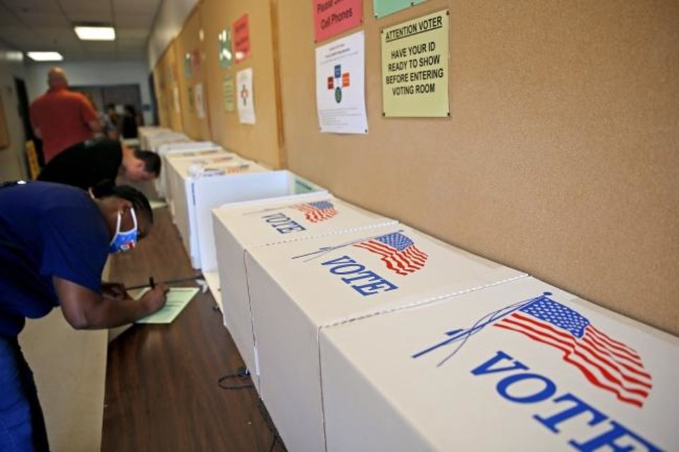 Photo -  Voters fill out a form before receiving their ballots during early voting at the Oklahoma County Election Board in Oklahoma City, Friday, June 26, 2020. [Bryan Terry/The Oklahoman]