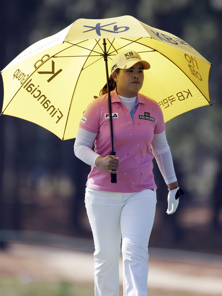 Photo - Inbee Park, of South Korea, uses an umbrella to avoid the heat as she walks down the 13th hole during the first round of the U.S. Women's Open golf tournament in Pinehurst, N.C., Thursday, June 19, 2014. (AP Photo/Bob Leverone)
