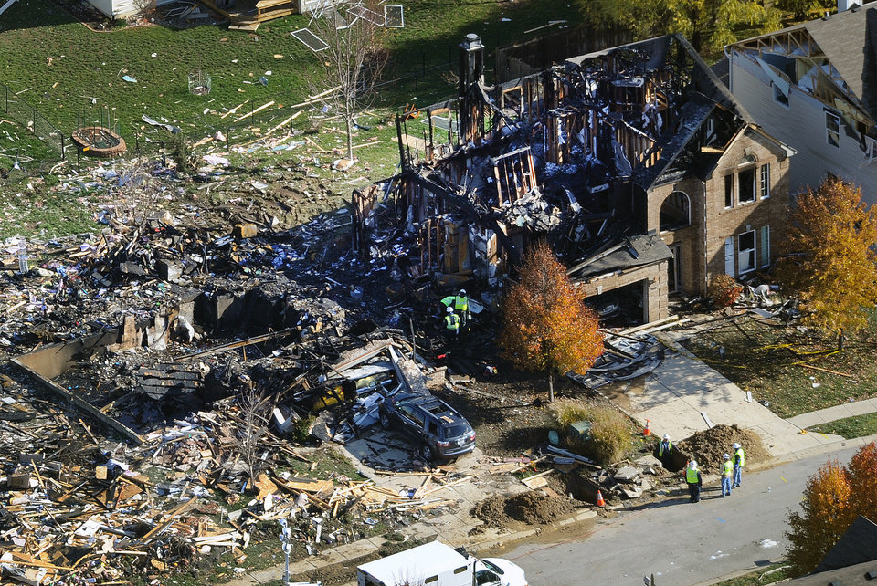 Photo -   Citizens Energy workers continue their investigation Monday, Nov. 12, 2012, at the site of an explosion at a house in Indianapolis. The search for what caused a massive, deadly explosion that rocked an Indianapolis neighborhood turned to natural gas Monday, with officials checking gas lines and a homeowner saying a problem furnace could be to blame. (AP Photo/WTHR Chopper 13/The Indianapolis Star, Matt Kryger)