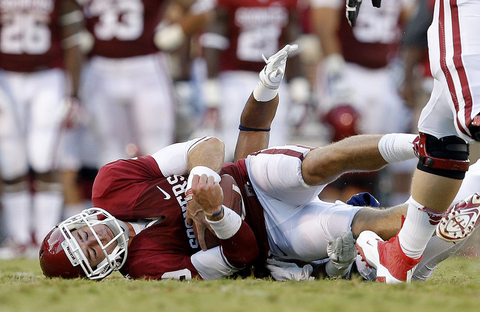 Photo - Oklahoma's Trevor Knight (9) is brought down during a college football game between the University of Oklahoma Sooners (OU) and the West Virginia University Mountaineers at Gaylord Family-Oklahoma Memorial Stadium in Norman, Okla., on Saturday, Sept. 7, 2013. Oklahoma won 16-7. Photo by Bryan Terry, The Oklahoman