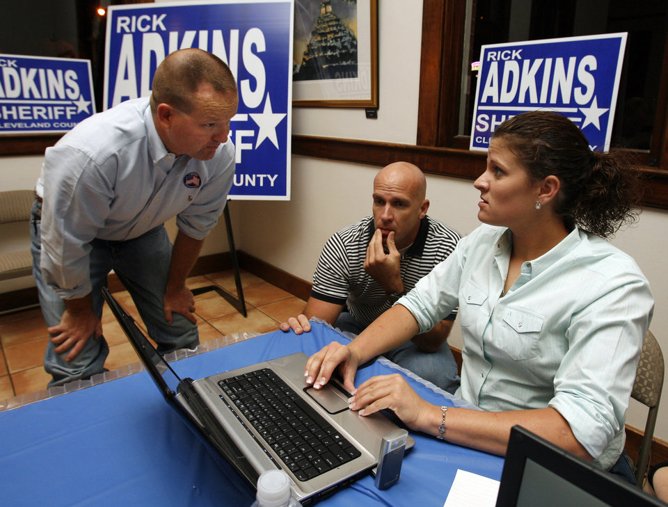 Photo - Rick Adkins, candidate for Cleveland County Sheriff (left), checks election returns with campaign manager Todd Carpenter and Ashley Cusack on Tuesday, Nov. 4, 2008, in Norman, Okla.    Steve Sisney, The Oklahoman