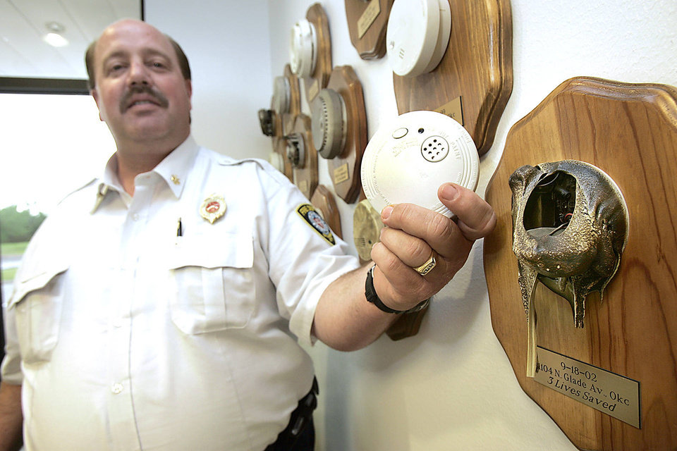 Oklahoma City Fire Department Battalion Chief Tim Adams displays a new smoke alarm next to smoke alarms that saved lives in Oklahoma City, Oklahoma April 29, 2009. <strong>Steve Gooch - The Oklahoman</strong>