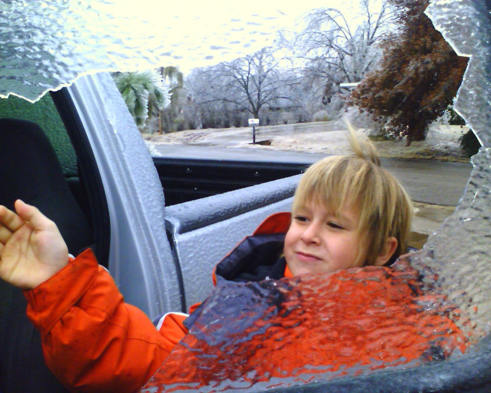 Kash Allen Kirkpatrick breaking ice off window so we can go for a drive the day of the icestorm.. It was a big surprise looked like a tornado hit the neighborhood for sure...<br/><b>Community Photo By:</b> Tama kirkpatrick<br/><b>Submitted By:</b> Tama, Midwest