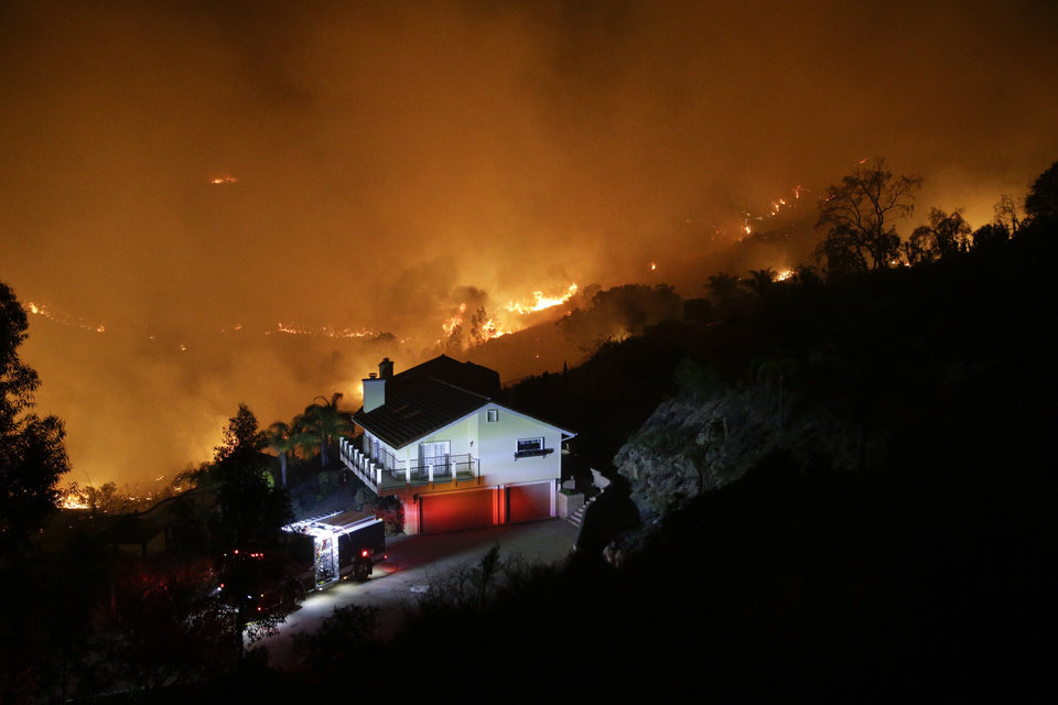 Photo - AP10ThingsToSee - A wildfire burns near a home on Wednesday, May 14, 2014, in San Marcos, Calif. Flames engulfed suburban homes and shot up along canyon ridges in one of the worst of several blazes that broke out Wednesday in Southern California during a second day of a sweltering heat wave. (AP Photo)
