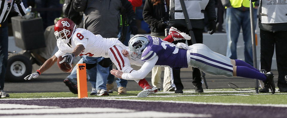 Oklahoma's Jalen Saunders (8) comes up short of the goal line on a punt return as Kansas State 's Mark Krause (38) forces him out during an NCAA college football game between the Oklahoma Sooners and the Kansas State University Wildcats at Bill Snyder Family Stadium in Manhattan, Kan., Saturday, Nov. 23, 2013. Oklahoma won 41-31. Photo by Bryan Terry, The Oklahoman