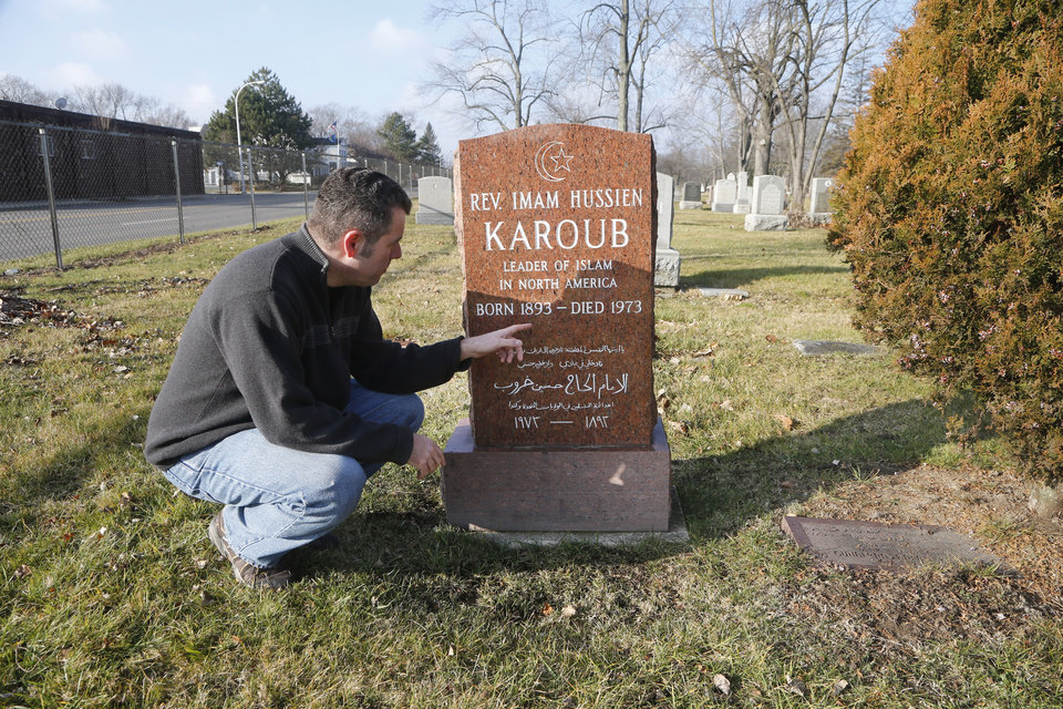 In this Dec. 18, 2012 photo, Detroit Associated Press reporter Jeff Karoub looks at the tombstone of his grandfather, The Rev. Imam Hussien Karoub, in Berkley, Mich. (AP Photo/Carlos Osorio)