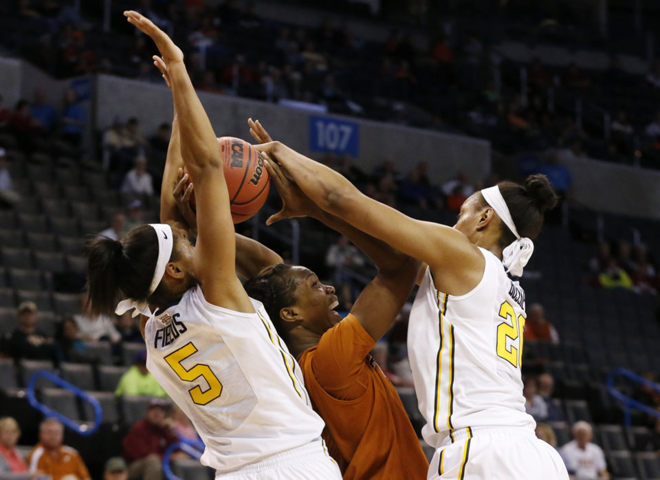 Photo - West Virginia forward Averee Fields (5) and center Asya Bussie (20) defend against Texas forward Nneka Enemkpali, center, in the second half of an NCAA college basketball game in the semifinals of the Big 12 Conference women's tournament in Oklahoma City, Sunday, March 9, 2014. West Virginia won 67-60. (AP Photo/Sue Ogrocki)