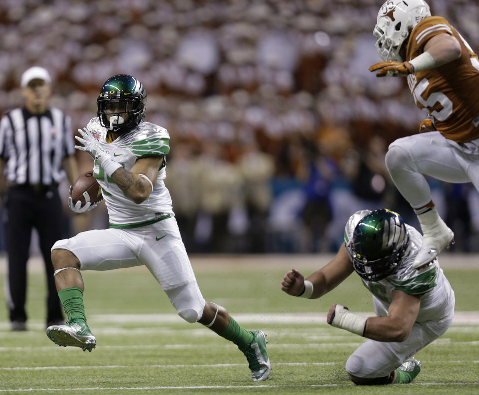 Oregon's Thomas Tyner, left, rushes as Texas' Dalton Santos pursues during the second quarter of the Valero Alamo Bowl NCAA college football game, Monday,  Dec. 30, 2013, in San Antonio. (AP Photo/Eric Gay)