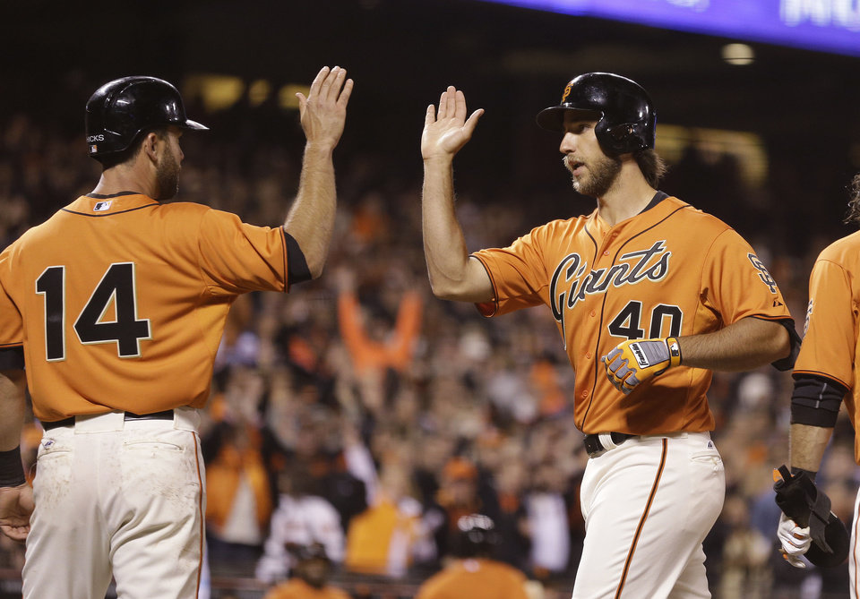 Photo - San Francisco Giants' Madison Bumgarner, right, is greeted by teammate Brandon Hicks, left, after hitting a grand slam off Colorado Rockies starting pitcher Jorge De La Rosa during the fourth inning of a baseball game Friday, April 11, 2014, in San Francisco. (AP Photo/Eric Risberg)