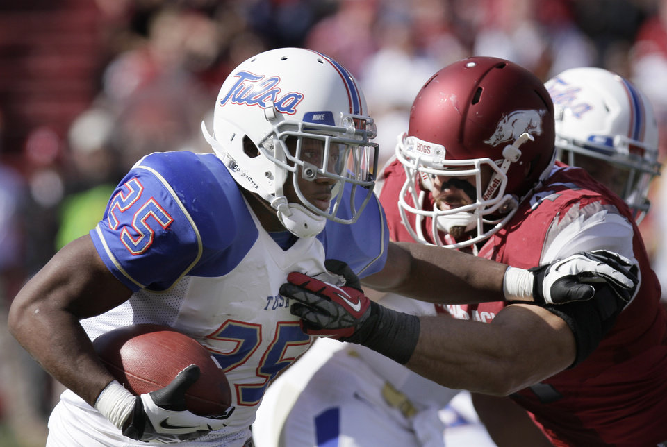 Tulsa running back Ja'Terian Douglas (25) pushes past Arkansas defensive end Austin Flynn (41) during the first half of an NCAA college football game in Fayetteville, Ark., Saturday, Nov. 3, 2012. (AP Photo/Danny Johnston)