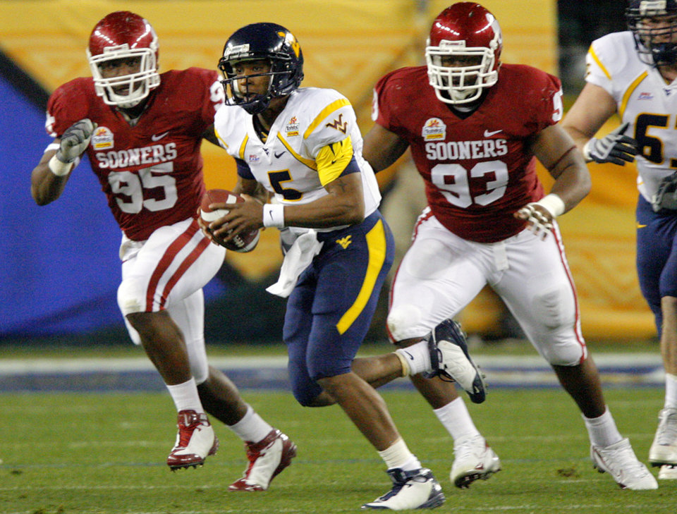Photo - West Virginia quarterback Patrick White (5) take the ball up field against the Oklahoma defense during the first half of the Fiesta Bowl college football game between the University of Oklahoma Sooners (OU) and the West Virginia University Mountaineers (WVU) at The University of Phoenix Stadium on Wednesday, Jan. 2, 2008, in Glendale, Ariz. 