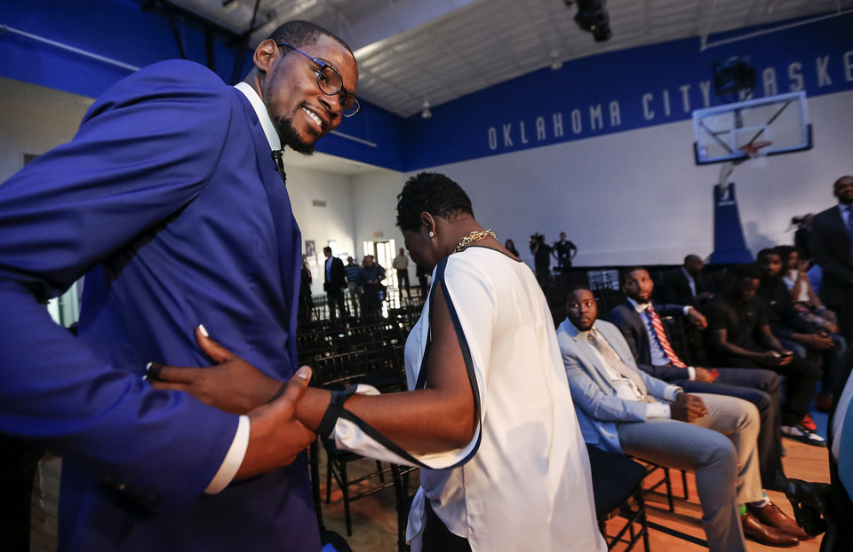 Photo - Kevin Durant smiles as he walks away after hugging his mother Wanda Pratt during a news conference announcing Oklahoma City Thunder's Kevin Durant as the winner of the 2013-14 Kia NBA Basketball Most Value Player Award in Oklahoma City, Okla. on Tuesday, May 6, 2014. Photo by Chris Landsberger, The Oklahoman