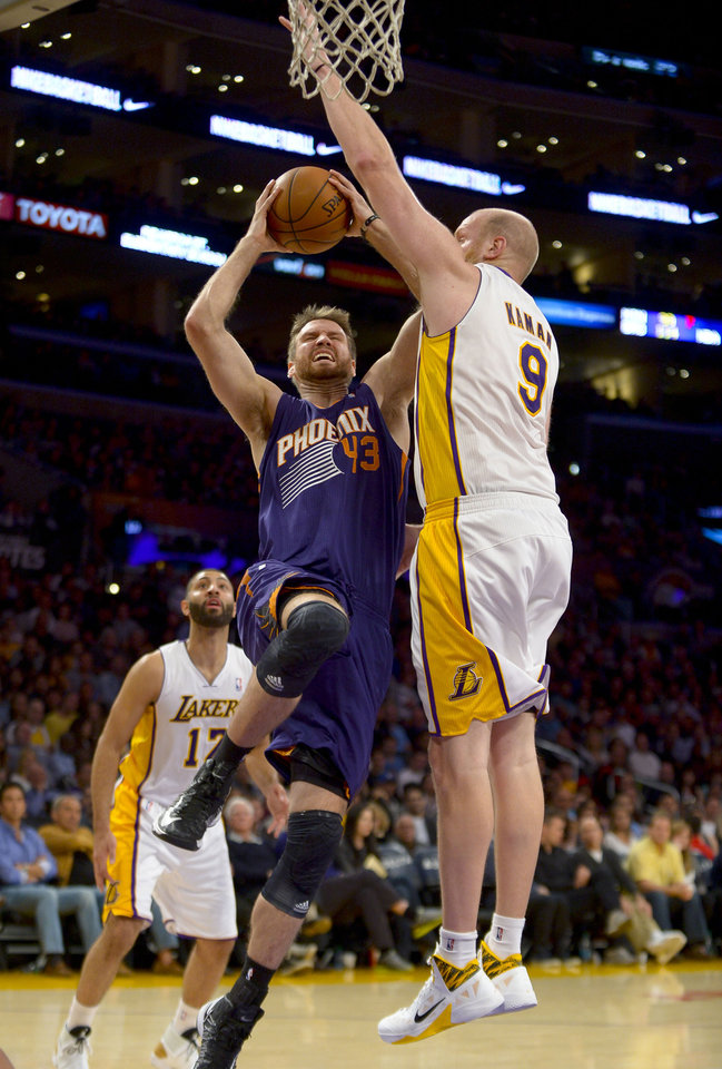 Photo - Phoenix Suns forward Shavlik Randolph (43) battles Los Angeles Lakers center Chris Kaman (9) as he goes to the basket in the first half of an NBA basketball game, Sunday, March 30, 2014, in Los Angeles.(AP Photo/Gus Ruelas)