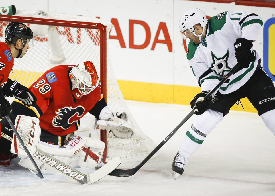 Dallas Stars' Rich Peverley, right, tries to get the puck past Calgary Flames goalie Reto Berra, from Switzerland, during first-period NHL hockey game action in Calgary, Alberta., Thursday, Nov. 14, 2013. (AP Photo/The Canadian Press, Jeff McIntosh)