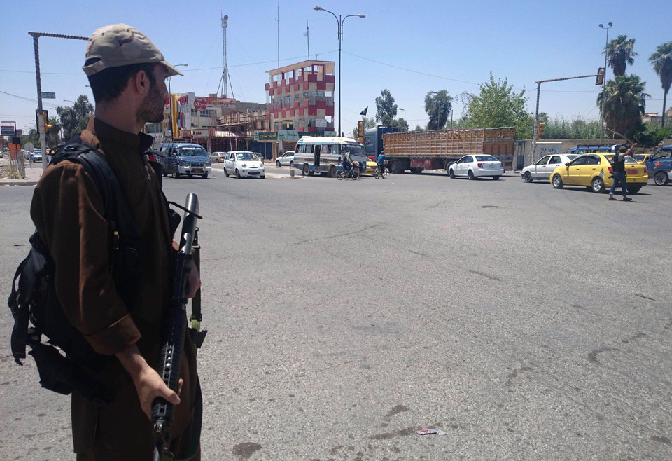 Photo - A fighter with the al-Qaida-inspired Islamic State of Iraq and the Levant (ISIL) takes control of a traffic intersection in the northern city of Mosul, 225 miles (360 kilometers) northwest of Baghdad, Iraq, Sunday, June 22, 2014. Sunni militants on Sunday captured two border crossings, one along the frontier with Jordan and the other with Syria, security and military officials said, as they pressed on with their offensive in one of Iraq's most restive regions. (AP Photo)