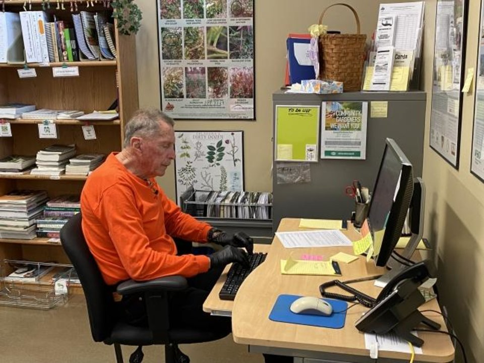 Photo -  John Walters, call center committee chairman for the Oklahoma County Master Gardeners, takes calls from people with gardening questions at the Oklahoma County Extension Center. [PROVIDED]
