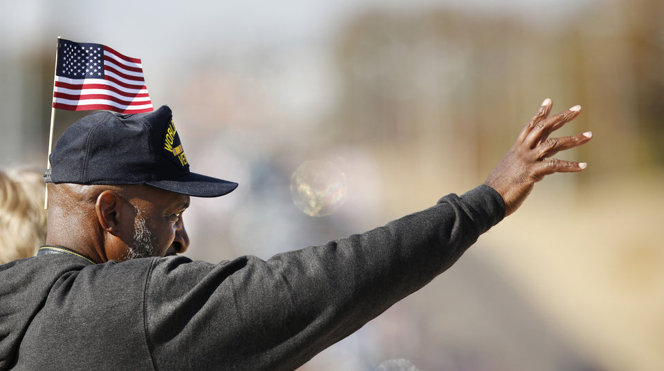 Photo - Richard McQuillar waves to people marching in Midwest City Veteran's Day Parade on Friday, Nov. 10, 2017. McQuillar is  wearing a World War II era veteran's hat to honor his late father-in-law who was a member of a B-26 bomber crew flying combat missions over Italy, he said. McQuillar spent 28 years in the Air Force and is now retired. He said his wife was in the Air Force for 21 years. Photo by Jim Beckel, The Oklahoman