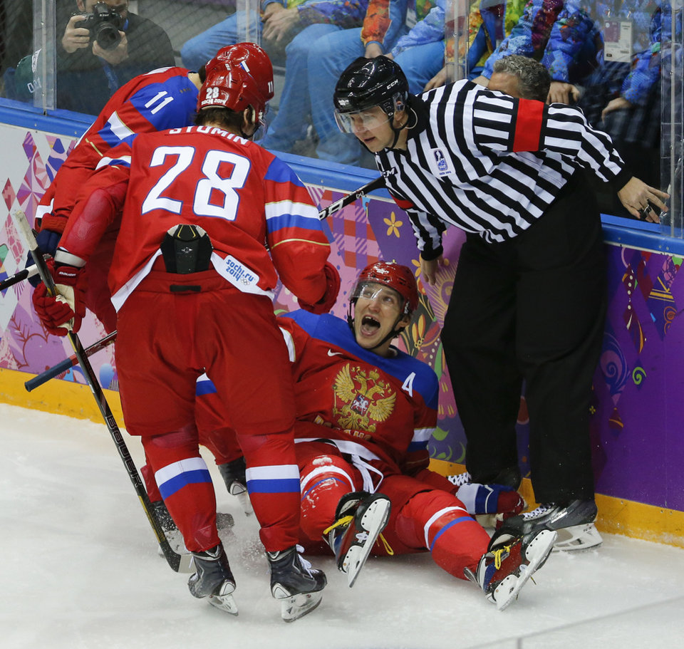 Photo - Russia forward Alexander Ovechkin reacts with forward Alexander Syomin and forward Yevgeni Malkin after scoring a goal against Slovenia in the first period of a men's ice hockey game at the 2014 Winter Olympics, Thursday, Feb. 13, 2014, in Sochi, Russia. (AP Photo/Mark Humphrey)