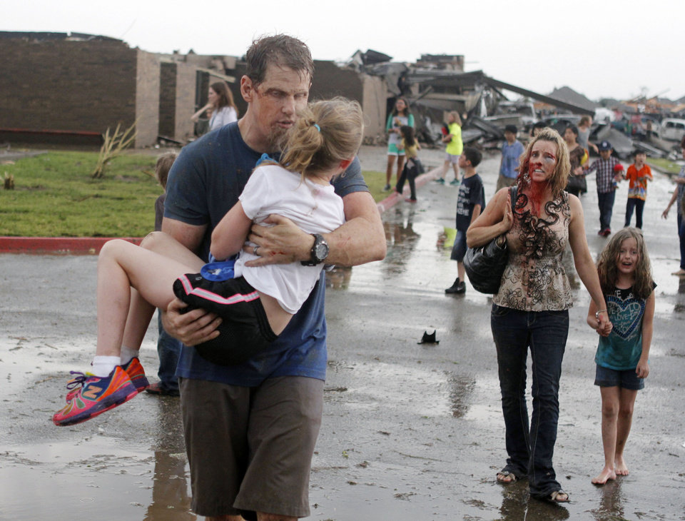 Teacher Ledonna Cobb walks with a student while husband Steve Cobb carries their daughter Jordan away from Briarwood Elementary school after a tornado destroyed the school in Moore, OK, Monday, May 20, 2013. Near SW 149th and Hudson. By Paul Hellstern, The Oklahoman