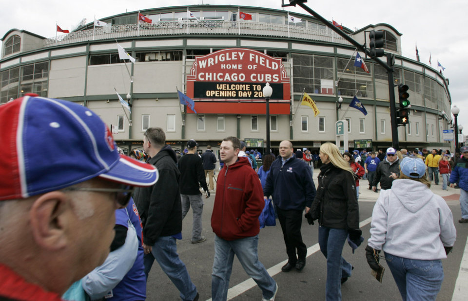 Photo - FILE - In this April 7, 2007 file photo, Chicago Cubs fans gather on opening day outside Wrigley Field in Chicago. Chicago's Wrigley Field, New Orleans' Saenger Theatre and a historic Los Angeles' shipbuilding center have joined a list of sites being saved thanks to the efforts of historic preservationists in 2013. (AP Photo/M. Spencer Green, File)