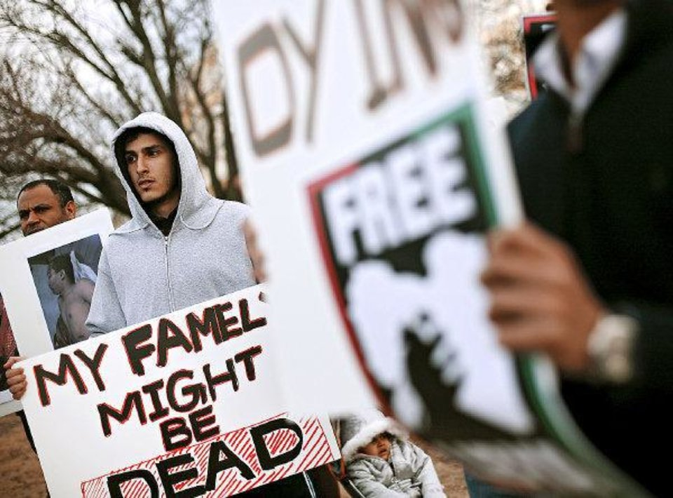 Photo - Ameen Emneina (left) holds a sign as he joins other Libyan immigrants and students protesting Moammar Gadhafi and the current situation in Libya at 23rd and Classen in Oklahoma City on Monday Feb. 21, 2011. Photo by John Clanton, The Oklahoman ORG XMIT: KOD