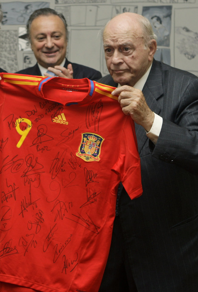 Photo - FILE - In this Nov. 13, 2009 file photo, former soccer player and honorary president of Real Madrid, Alfredo Di Stefano, right, receives a Spanish soccer shirt while being applauded by the Argentine ambassador to Spain, Carlos Bettini, during a homage to  Di Stefano for his contribution to sport, at the Argentine Embassy in Madrid. Di Stefano, whose goals placed him alongside the all-time great players and propelled Real Madrid to five straight European Champions Cups, has died on Monday, July 7, 2014. He was 88.  (AP Photo/Paul White, File)