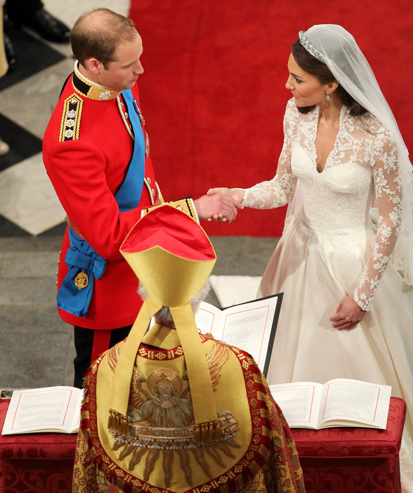 Photo - Prince William and Kate Middleton, hold hands in front of the Archbishop of Canterbury at Westminster Abbey during their wedding service in central London, Friday April 29, 2011. (AP Photo/Andrew Milligan, Pool)  ORG XMIT: RWAJP117