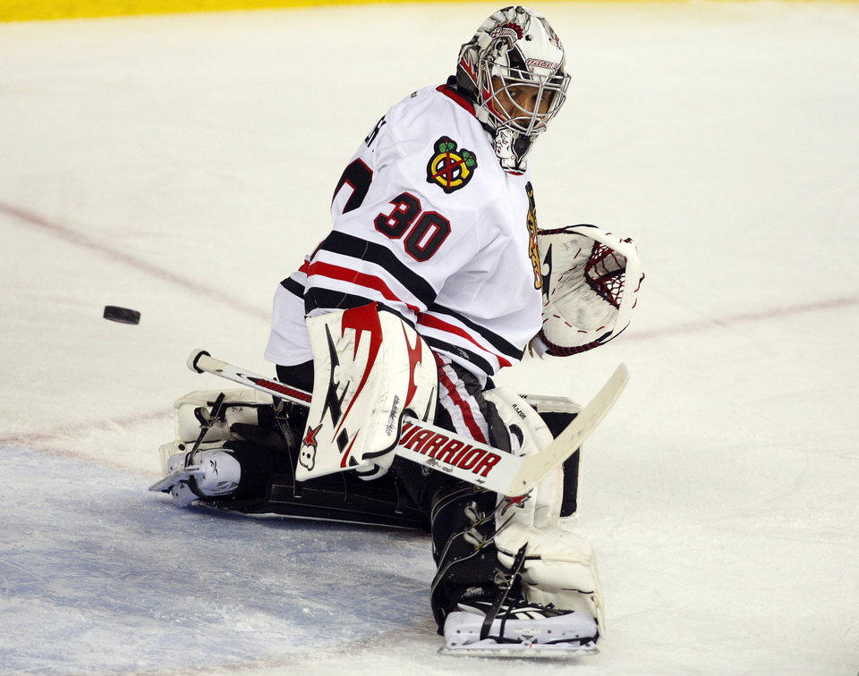 Photo - Chicago Blackhawks goalie Ray Emery deflects the puck against the Calgary Flames during overtime of an NHL hockey game in Calgary, Alberta, Saturday, Feb. 2, 2013. The Blackhawks defeated the Flames 3-2 in a shootout. (AP Photo/The Canadian Press, Jeff McIntosh)