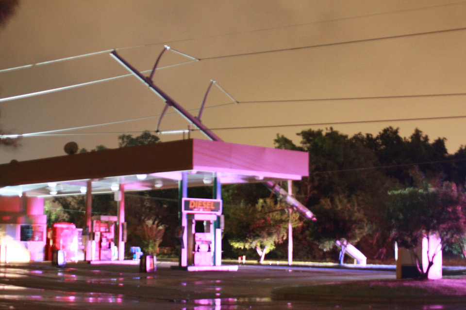 Downed power lines lean against the roof of a gas station pavilion at 164th and Western. By TODD FRASER/for The Oklahoman