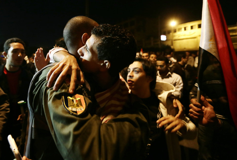 An Egyptian protester hugs an Egyptian army soldier after the army left their position outside the presidential palace, in Cairo, Egypt, Friday, Dec. 7, 2012. Egyptian protesters broke through a barbed wire barricade that was keeping them from getting closer to the presidential palace on Friday. Egypt\'s political crisis spiraled deeper into bitterness and recrimination Friday as thousands of Islamist backers of the president vowed vengeance at a funeral for men killed in bloody clashes earlier this week and large crowds of the president\'s opponents marched on his palace to increase pressure after he rejected their demands. (AP Photo/Hassan Ammar)